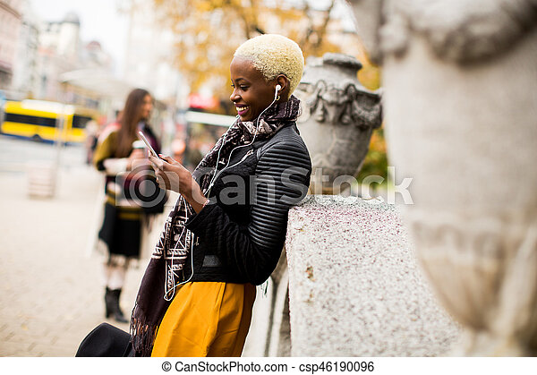 African american and caucasian woman posing outside with mobile phone and a cup of coffee to go in autumn - csp46190096