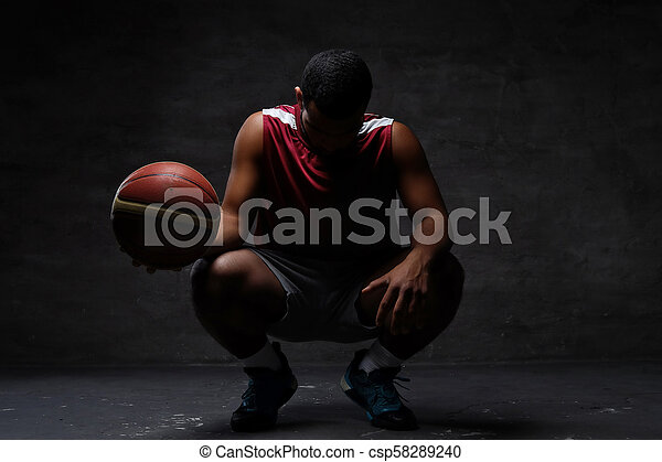 African-American basketball player in sportswear squatting with a ball on a dark background. - csp58289240