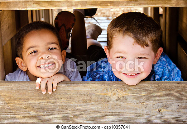 African-American child and caucasian child playing together on playground - csp10357041