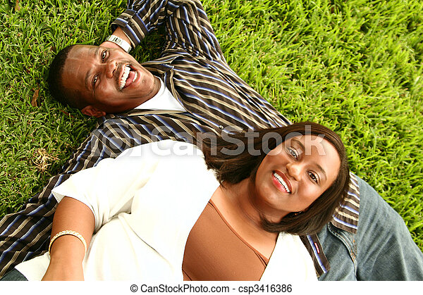 African American Couple Laying On The Grass - csp3416386