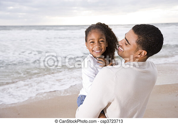 African-American dad hold little girl at beach - csp3723713