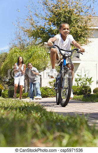 African American Family WIth Boy Riding Bike & Happy Parents - csp5971536