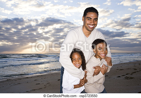 African-American father and two children on beach - csp3723550