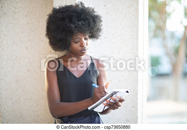 African American lady writing notes leaning on a wall of a concrete building - csp73650880