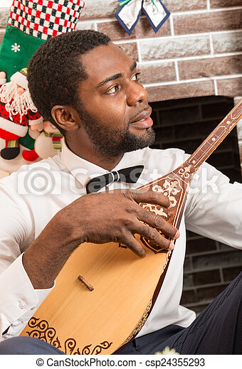 African American man with Musical instrument Dombra by fireplace  Christmas  and New Year