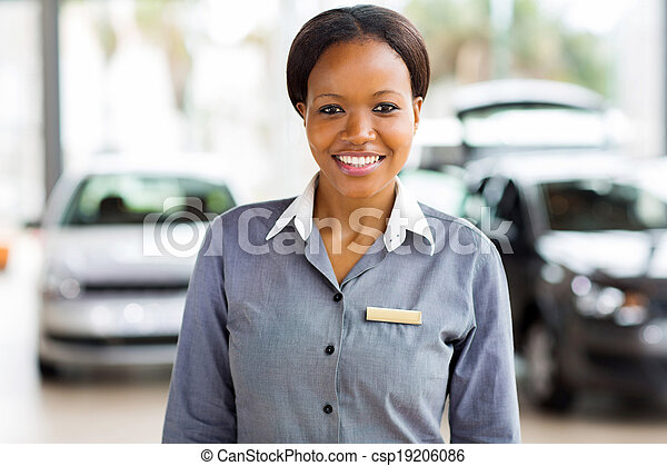 african american saleswoman standing at car dealership - csp19206086