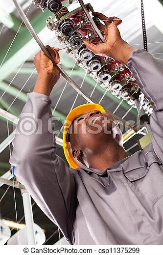 african american textile technician repairing - csp11375299