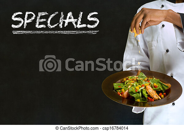 African American woman chef with chalk specials sign on blackboard background - csp16784014