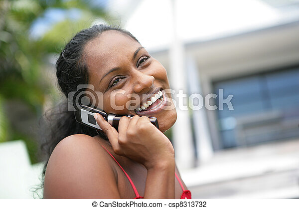 African American woman laughing during call - csp8313732