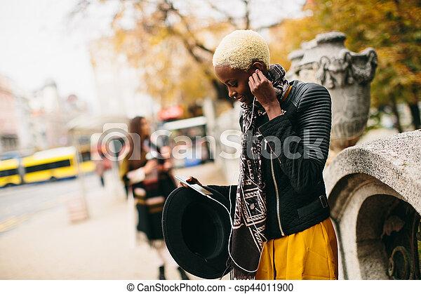 African american woman listening music outdoor - csp44011900