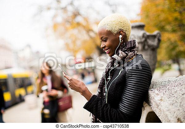 African american woman listening music outdoor - csp43710538