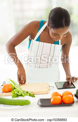 african american woman looking at tablet computer for a recipe - csp15356893
