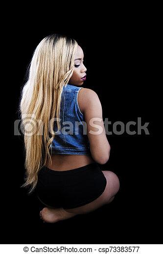 African American Woman Sitting Against Dark Background Blue Vest - csp73383577