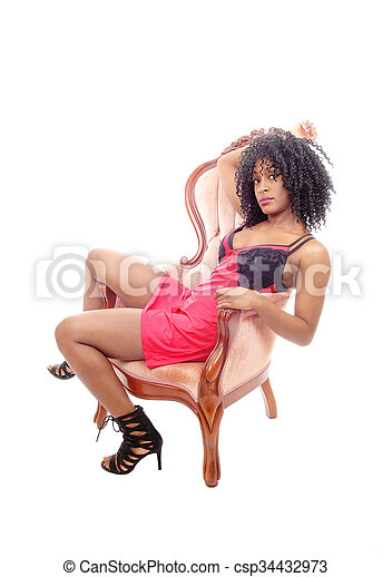 African American woman sitting in armchair. - csp34432973