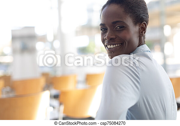 African-american woman sitting in conference room - csp75084270