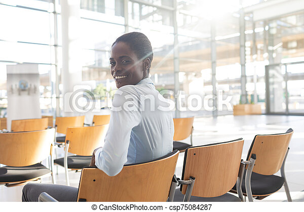 African-american woman sitting in conference room - csp75084287