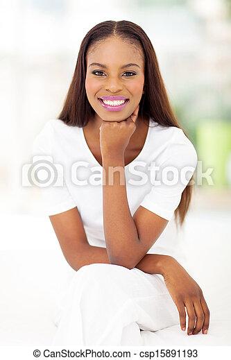 african american woman sitting in bedroom - csp15891193