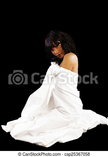 African American Woman Sitting On Floor In White Sheet - csp25367058