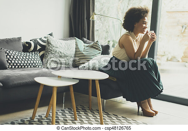 African american woman sitting on sofa with cup of coffee - csp48126765