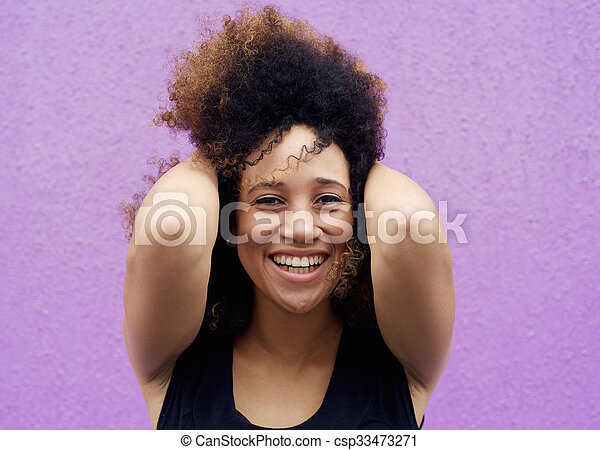 African american woman smiling with hand in hair - csp33473271
