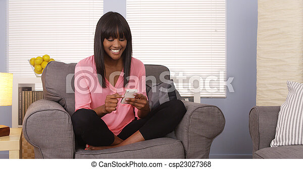 African American woman using smartphone at home - csp23027368