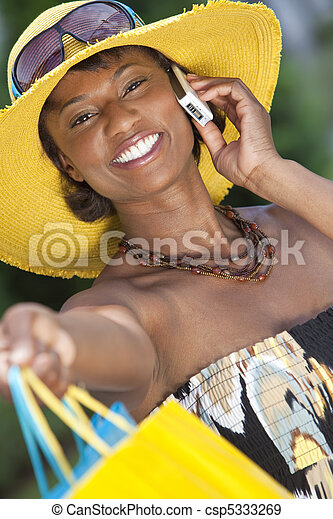 African American Woman With Fashion Shopping Bags on Cell Phone - csp5333269
