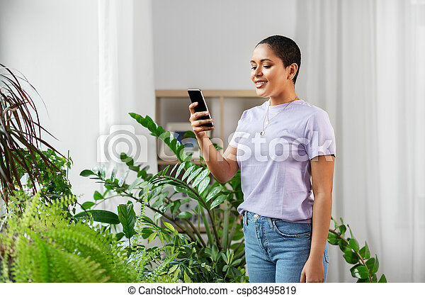 african american woman with smartphone at home - csp83495819