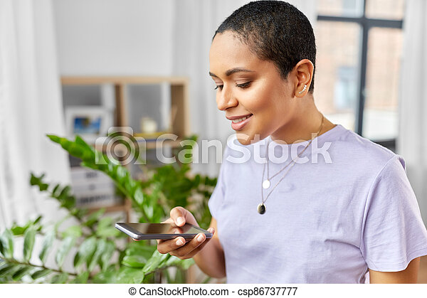 african american woman with smartphone at home - csp86737777