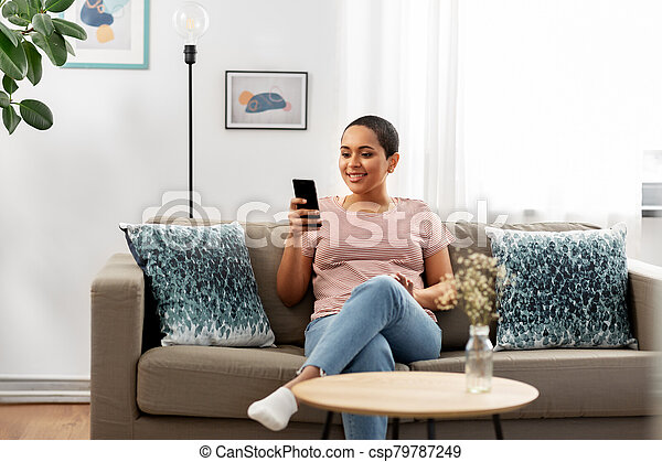 african american woman with smartphone at home - csp79787249