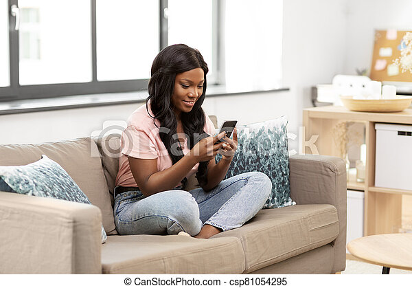 african american woman with smartphone at home - csp81054295