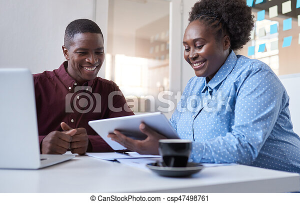 African colleagues working with a tablet in business office - csp47498761
