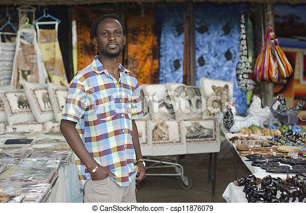 african curio salesman vendor in front of wildlife items - csp11876079