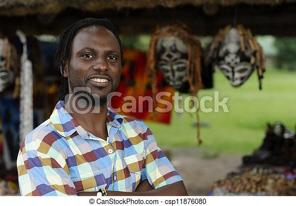 African curio salesman vendor  in front of ethnic masks - csp11876080