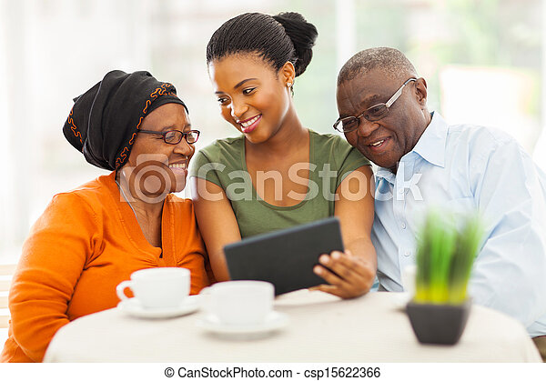 african family at home using tablet pc - csp15622366