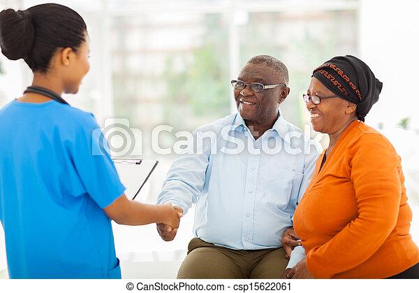 african female nurse greeting senior couple - csp15622061