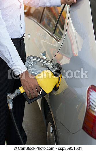 african male pumping gas at station - csp35951581