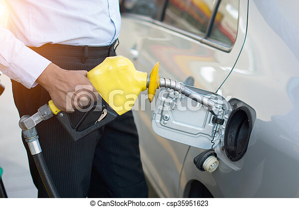 african male pumping gas at station - csp35951623