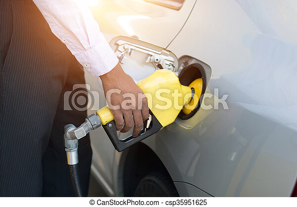 african male pumping gas at station - csp35951625