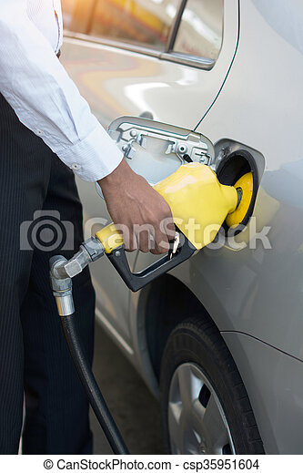 african male pumping gas at station - csp35951604