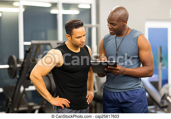 african personal trainer helping man to fill the membership form - csp25617603