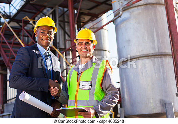 african refinery manager handshaking with senior worker - csp14685248