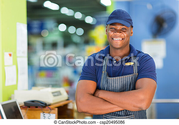 african supermarket cashier standing at checkout - csp20495086
