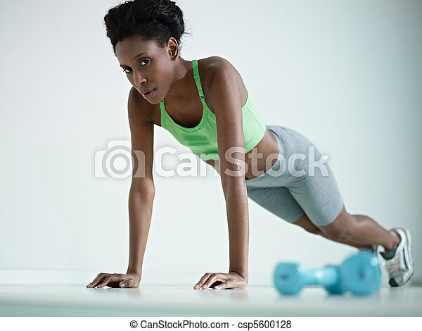 african woman doing series of push-ups in gym - csp5600128