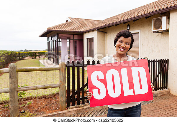 african woman holding sold sign in front of house - csp32405622