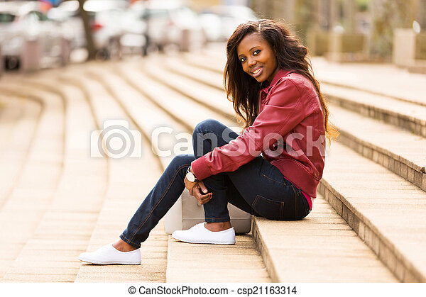 african woman outdoors sitting on steps - csp21163314
