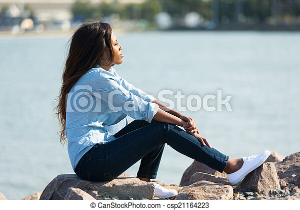 african woman sitting by the harbour - csp21164223
