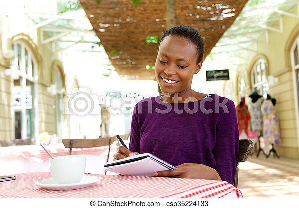 African woman writing in a cafe portrait of attractive young african woman writing in a cafe csp35224133 publicscrutiny Gallery