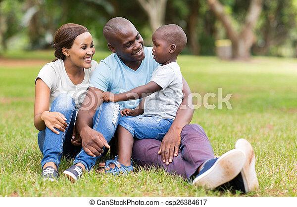 Die junge afrikanische Familie sitzt draußen - csp26384617