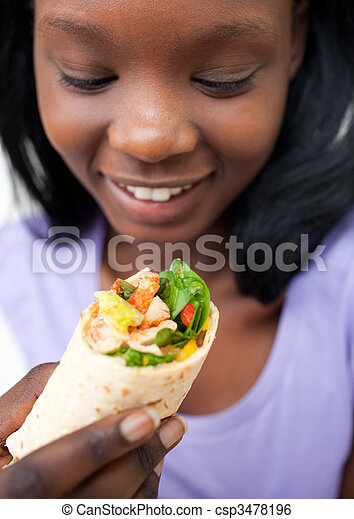Afro-american young woman eating a wrap - csp3478196