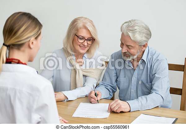 Aged couple signing contract making investment at meeting with a - csp55560961